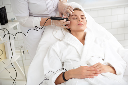 Serious girl getting treatment of skin with digital device. She closing eyes. Cosmetologist keeping it in arm