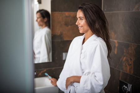 Side view happy female holding toothbrush while locating in bathroom. She reflecting in mirror and leaning on sink Stock Photo