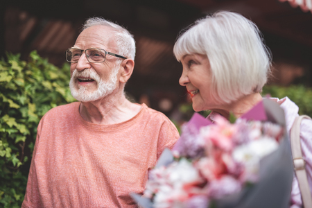 Side view of smiling elderly man standing with spouse on street. Happy woman is holding bouquet of flowers and looking at male with love and delight