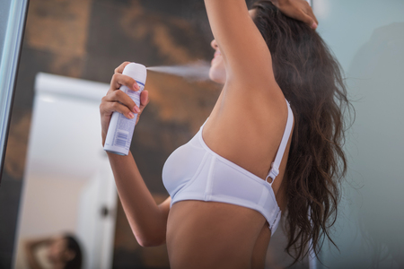 Outgoing woman applying antiperspirant on body while wearing bra. She standing in apartment. Skin care concept