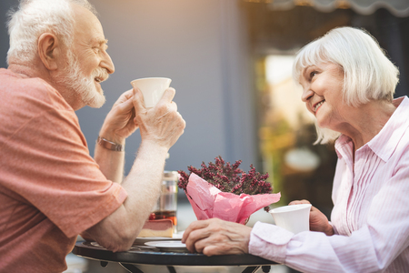 Side view profile of happy senior couple drinking tea in cafe outdoors. They are laughing with delight while having pleasant chat