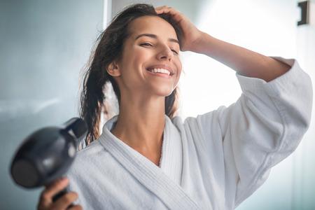Portrait de femme souriante séchant les cheveux avec appareil numérique. Elle tient les cheveux avec la main Banque d'images