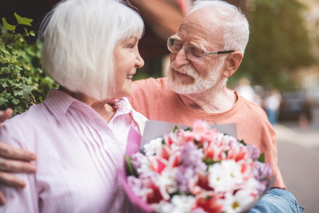 My love. Side view of delighted senior man and woman standing outdoors and smiling. Elderly female is holding beautiful bunch of flowers in hands Stock Photo