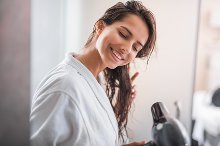 Portrait of beaming woman drying hair with modern digital device Banque d'images