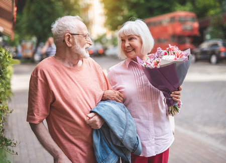 Side view of happy couple standing on street. Elderly female is holding beautiful bunch of flowers presented by male. They are looking at each other and smiling