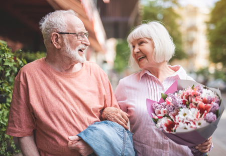 Side view of smiling senior male and female walking side by side outside after date. Mature woman is carrying bouquet of flowers and looking at man with sincere smile