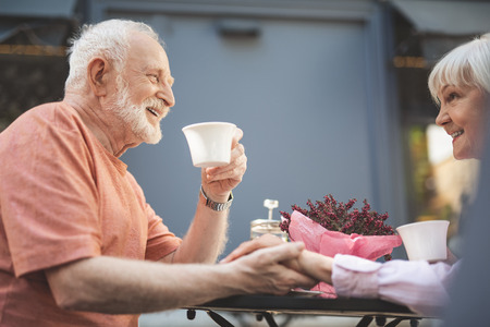 Side view of smiling senior male drinking tea and holding mature woman hand. She is touching cup and looking at him with care and love