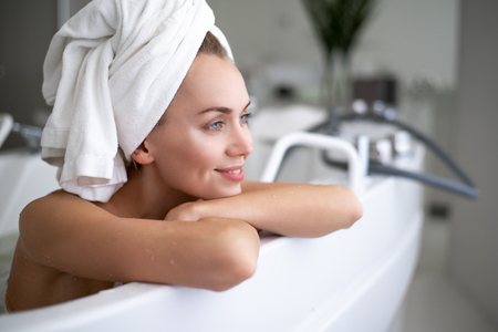 Side view outgoing lady leaning on bath while looking away. Pleasure during procedure concept Stock Photo