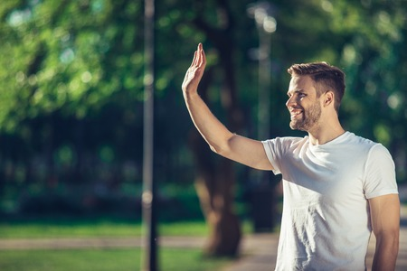 Side view of delighted male standing outdoors and waving hand to his friend. He is joyful to meet his acquainted by chance. Copy space in left side
