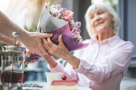 Focus on male hands holding bunch of flowers to smiling mature lady. She is taking present with pleasure and sincere gratitude