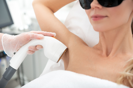 Optimistic woman having depilation of armpit. Cosmetologist making it with digital device