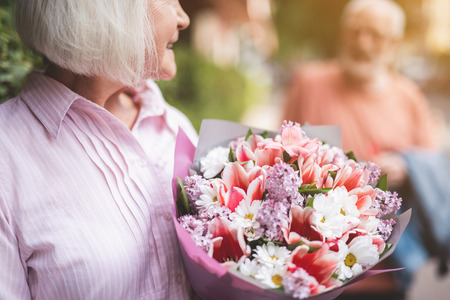 Focus on beautiful bunch of flowers in female hands. She is happy and joyful after date. Old male is on background