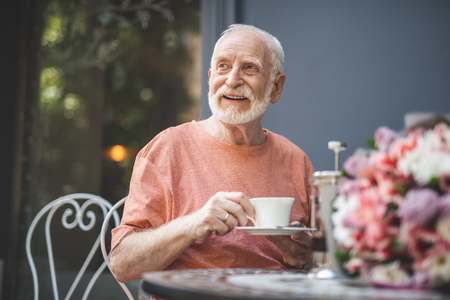 Waist up portrait of happy mature man sitting at table in cafe outdoors and holding cup of hot drink. He is looking sideways with delight while waiting for woman with beautiful flowers beside him Stock Photo