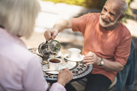 Here you are. Waist up portrait of happy mature male pouring hot drink into cup while having dinner with wife. They are sitting at table and admiring precious time together Foto de archivo - 104738998