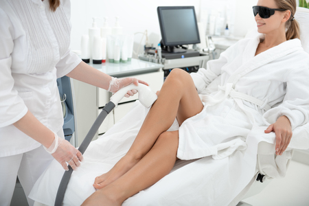 Positive girl leaning on coach while having hair removal in clinic. Doctor making it with digital device. She wearing glasses