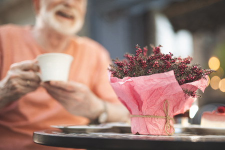 Focus on bunch of beautiful flowers standing on table outdoors. Senior male is sitting and holding cup with hot drink with wide smile and joy