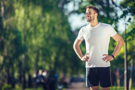 Full length of smiling attractive athlete standing and holding hands on waist. He is enjoying perfect weather for outdoor training. Copy space in left side 版權商用圖片