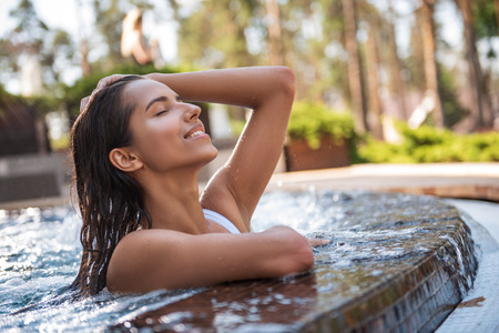 Side view beaming girl relaxing in swimming pool outside. She gesticulating hand while keeping head