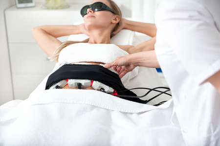 Satisfied girl in spectacles lying during special anti-cellulite massage. Cosmetologist setting digital device to her