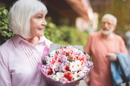 Side view profile of smiling senior lady standing on street with bunch of flowers in hands.  She is satisfied after saying goodbye to her man on background smiling to her Stock fotó