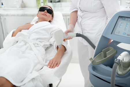 Positive female patient locating on coach while getting depilation with special equipment
