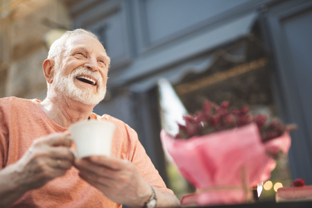 Low angle waist up portrait of delighted mature male sitting at table outside. He is holding cup of hot drink and looking with pleasure and content. Copy space in right side Stock Photo