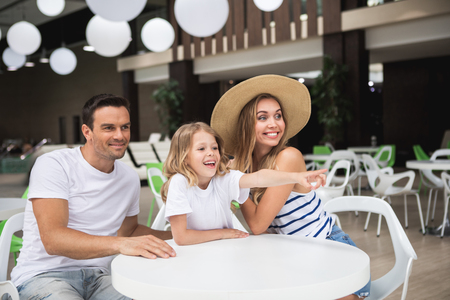 Look there. Waist up portrait of cheerful family sitting at table in bar. Small child is pointing with finger and smiling while woman and man are looking sideways with delight Stock Photo
