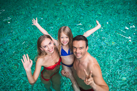 Waist up portrait of delighted mother and father holding daughter in water.  They are standing and bonding to each other with love and joy admiring vacation together Stock Photo
