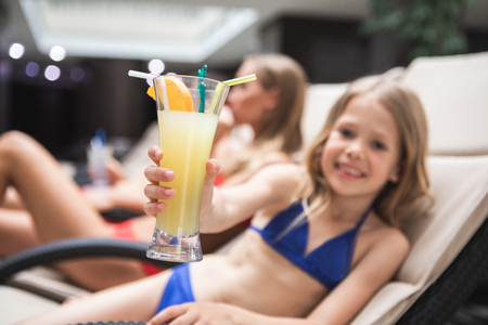Try it. Close up focus on kid hand holding glass of cocktail. Smiling child is relaxing with parents by pool. Mother lying on deck chair is on background Stok Fotoğraf