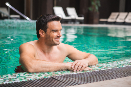Side view of happy attractive man swimming in pool. He is leaning with hands against poolside and looking sideways with delight Stock Photo