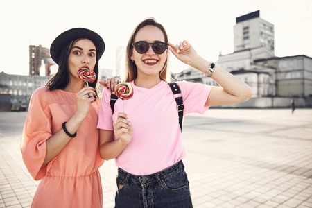 Portrait of beaming lady touching sunglasses while keeping candy in hand. She standing near glad female friend eating sweet outdoor. Happy comrades having fun outside concept