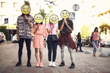 Full length portrait of positive girls and men with emoji faces standing at street
