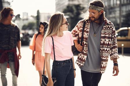 Uomo barbuto ottimista con capelli lunghi che comunica con giovane donna in uscita. Camminano lungo la strada