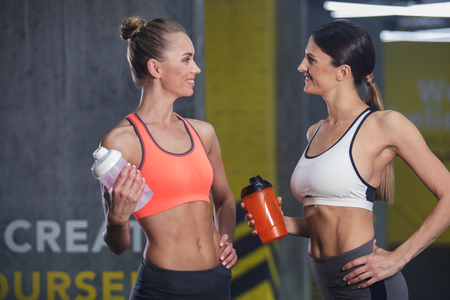 Cheerful sporty girlfriends are talking while training in gym. They are standing and holding bottles of water while looking at each other. Communication during exercising concept