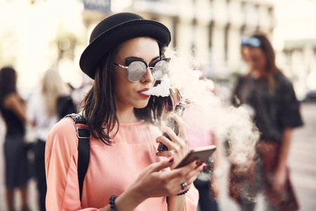 Portrait of orderly young lady smoking electronic cigarette while using contemporary phone outside