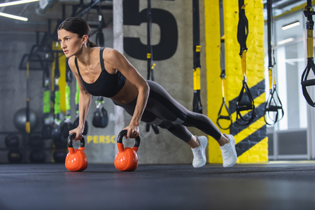 Athletic woman is straining in plank position. She is having hands on heavy weights and looking ahead. Female is doing crossfit training with equipment in fitness center Stock Photo