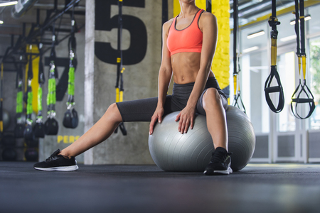 Low angle of shapely lady sitting on big ball. She is training with equipment in gym while wearing sneakers and sport clothes. Work out with outfit concept