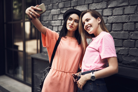 Portrait of beaming women taking selfie with contemporary phone while looking at it. They situating outdoor 写真素材