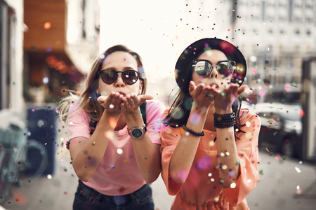 Portrait of cheerful ladies blowing confetti from hands. They situating on street during sunny day. Glad girl having fun, celebration concept Stock fotó - 105011243