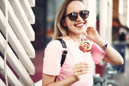 Portrait of happy girl tasting lollipops while gesticulating hand. She walking along street