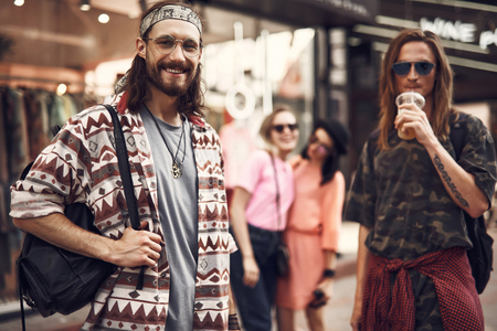 Portrait of beaming bearded male carrying bag while situating near glad comrade. He drinking cup of liquid