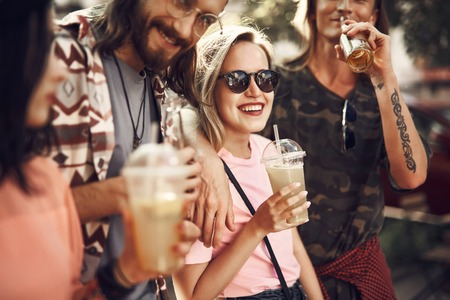 Beaming girls and outgoing males tasting appetizing beverage. They embracing together 写真素材