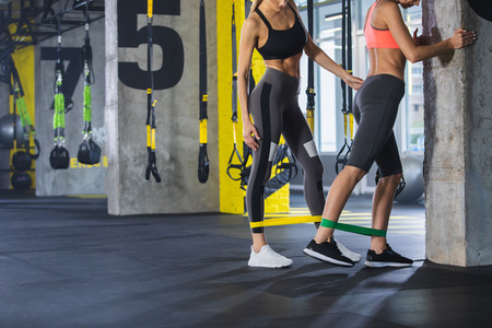 Sporty lady is exercising with personal trainer in gym and they are using latex band on ankles for straining. Girl is standing facing wall while coach woman is standing near and controlling correct outfit exploiting. Copy space in left side