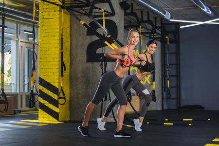 Couple of slim joyful females are training with trx system in gym. They are doing chest press by grabbing straps handles and extending arms forward. Girls are exercising together for improving strength and endurance Stock Photo