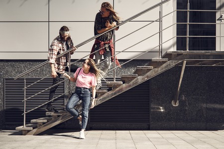 Full length beaming girl talking with cheerful male. Outgoing guys standing on stairs outside. Happy conversation of friends concept Stock Photo