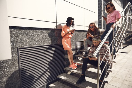 Portrait of orderly men and serious girls typing in modern phones while having rest on ladder. They locating at street