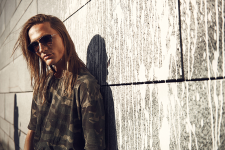 Portrait of serious male with long hair wearing modern sunglasses. He leaning against wall while locating outside. Copy space Stock fotó