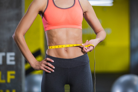 Close up of ripped woman belly wearing sport clothes. Slender girl is standing in gym and measuring size with centimeter tape. She is estimating abdominal muscles