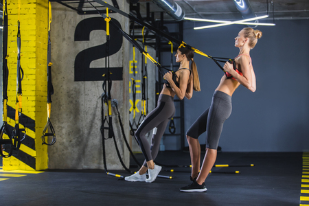 Two athletic women are having joint crossfit work out in gym. They are doing low rows together handling TRX straps. Both ladies together are straining synchronously for strengthen back Stock Photo