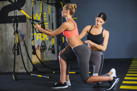 Athletic lady is doing lunges while holding TRX straps in sport studio. Woman coach is standing on one kneel near sportswoman and supervising exercising. Suspension work out for female concept